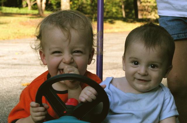 Children play in push car Come insegnare ai bambini il comportamento di condivisione